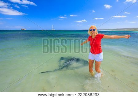 Happy blonde woman with open arms near an Australian Eagle Ray close to shore in Hamelin Bay, Margaret River Region, Western Australia. Female tourist enjoys big eagle sting rays a popular attraction.