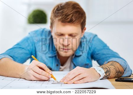 Very careful. Calm attentive smart engineer sitting at the table in his comfortable office and looking careful while drawing a straight line on a scheme