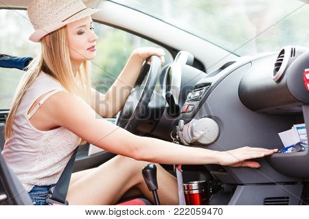 Distracted driver. Young attractive woman looking for something in vehicle interior while driving the car.