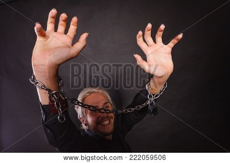 No freedom, social problems concept. Smiling man with chained hands, studio shot on dark grunge background