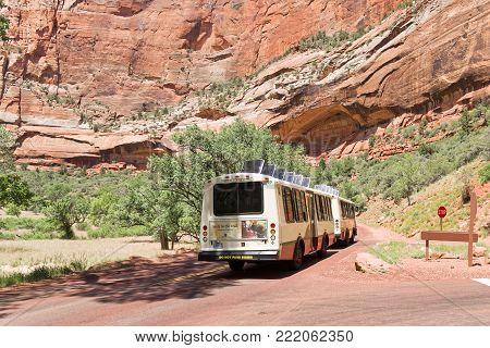 Springdale, Utah, USA - June 3, 2015: Zion Park Bus transports tourists inside the park at the Lodge. Zion National Park, Utah.