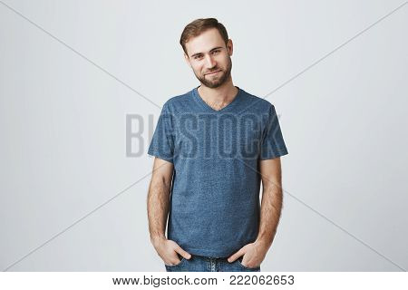Glad bearded young male happy to have date with girlfriend, being in good mood, dressed casually, isolated against gray studio background. Shot of good-looking unshaven happy man holding hands in pockets