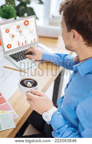 Hot drink. Smart responsible engineer drinking coffee while looking attentively at the screen of his modern devise and feeling interested in the new information