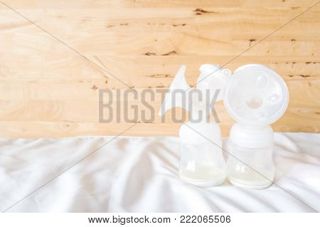 Bottles of automatic breast pump with fresh mother breast milk for baby on white bed sheet and wooden background in bedroom. Breast pump and store in refrigerator help breast milk stay fresh longer.