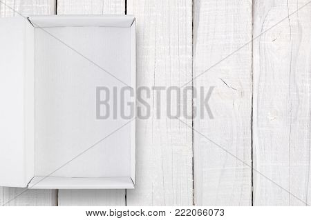 Opened white box with cover on white wooden background top view