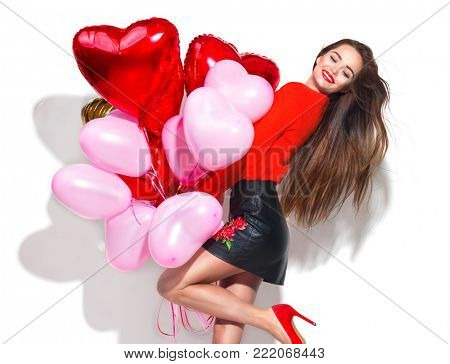 Valentine Beauty girl with colorful air balloons laughing, isolated on background. Beautiful Happy Young woman. holiday party. Joyful model having fun, playing and celebrating with red color balloon