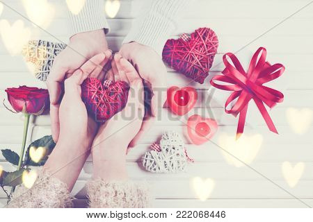 Valentine Gift. Young Couple Hands holding red heart gift over wooden background. St. Valentine's Day, Love concept. Top view, tabletop. Hands in Hands, romance, dating concept