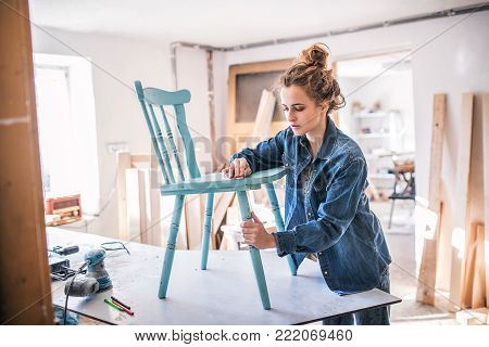 Small business of a young woman. Beautiful young woman worker in carpenter workroom. Old furniture restoration. poster