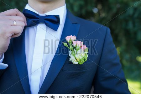 Stylish groom in blue jacket, white shirt with white and pink boutonniere. A golden wedding ring on a groom's finger.