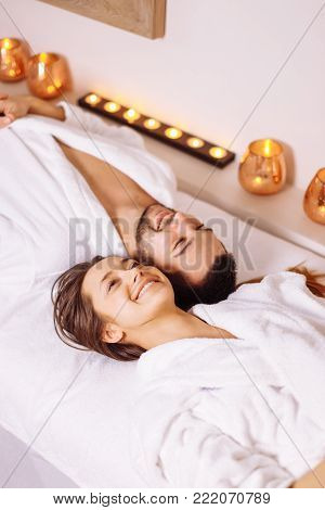 Beautiful couple relaxing in spa center lying on massage table