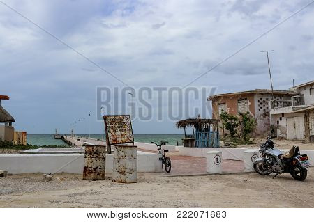 A bicycle and a motorcycle parked near a pier and old weather beaten houses near Progesso Yucatan Mexico 7 - 06 - 2017