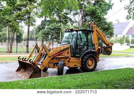 Yellow cabbed tractor with backhoe and muddy front loader on an upscale neighborhood street on a rainy day