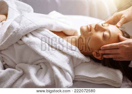 Calm girl having spa facial massage in luxurious beauty salon