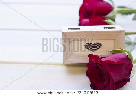 The concept of Love, Wedding, Proposal, Anniversary, St. Valentine's Day, Mother's Day with beautiful red velvet roses and decorative wooden casket in a close up, light wooden background
