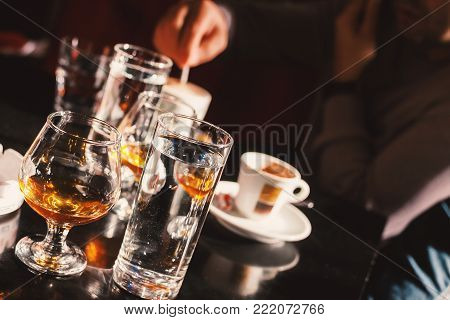 Glasses of alcohol drink and cups of coffee on cafe table, man is sitting in blurry background and talking on phone.