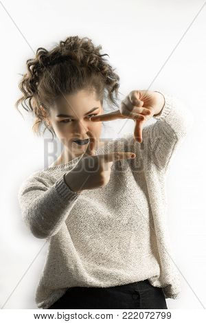 Beautiful young caucasian woman looking throw the fingers frame isolated on white background. Live outside the box concept.