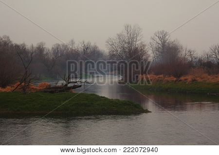 Winter landscape without snow, river and surroundings.