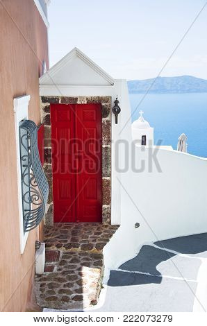 Traditional Greek architecture with a bright red door and a view of the blue sea. Santorini, Cyclades, Greece.