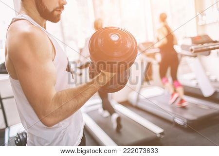 Muscular Bearded man during workout in the gym. Athlete muscular bodybuilder in the gym training biceps with dumbbell. Indoor fitness.