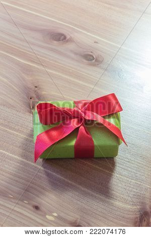 Tiny gift box wrapped in green paper with a big red satin bow, copy space, neutral wood background, vertical aspect