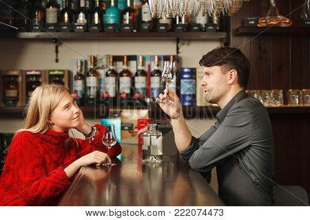 Bartender stands at bar counter and holds glass of rum and tells about it to girl-visitor that listen attentively with long shelves of alcohol drinks on background.