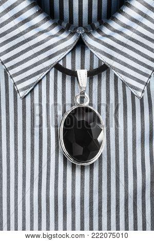 Black onyx medallion on black lace hanging over blue satin striped blouse
