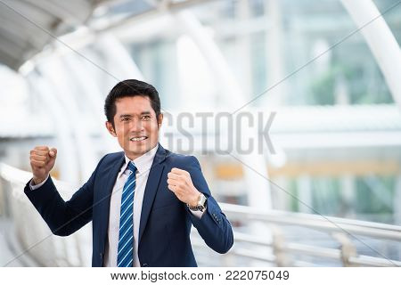 Successful Businessman with rise arms up celebrating, Successful business after good deal with partnership signed agreement. Business meeting and agreement concept.