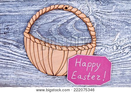 Plywood cut out basket for Easter, top view. Easter pink color card with inscription Happy Easter, old wooden background. The best wishes for Easter holiday.