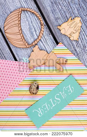 Easter card, wooden figurines, top view. Quail egg on colorful patterned sheets of paper, plywood rabbits and basket cutouts. Easter handmade decoration ideas.