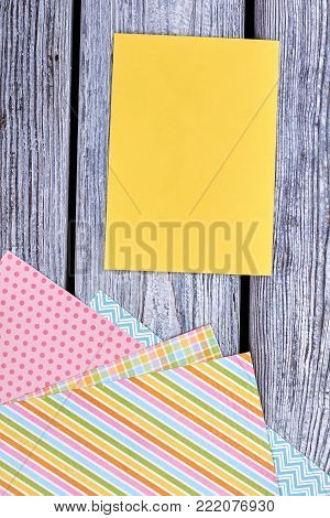 Blank card and patterned paper sheets. Set of colorful patterned paper for handmade craft on old wooden background. Stationery for handmade paper decorations for Easter holidays.