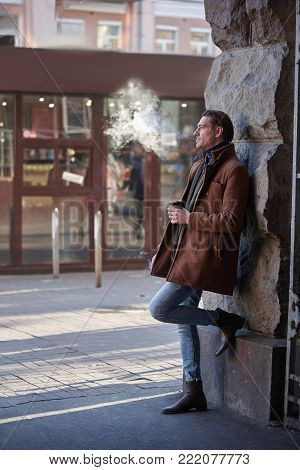 Full length side view pensive male drinking cup of delicious liquid while leaning against wall on street and smoking. Dreaminess concept
