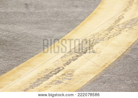 Cracks on yellow road paint from transportation.