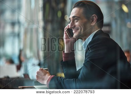 Side view happy male speaking by phone while sitting at table in cafe. He drinking mug of beverage. Relax and conversation concept