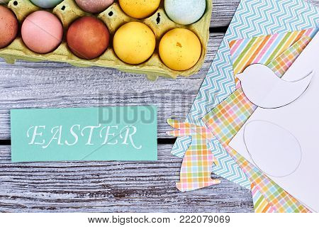 Easter card and painted eggs, top view. Colorful patterned sheets of paper, cut out paper figures, turquoise inscription Easter on old wooden background. Paper Easter decorations made at home.