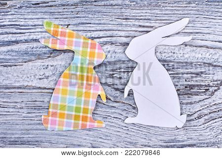 Paper rabbit cutouts, top view. Couple of white and patterned Easter bunnies on rustic wooden background. Papercut animalistic silhouettes for Easter holidays.