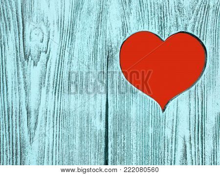 Red heart carved in a blue wooden board. Background. Postcard, valentine