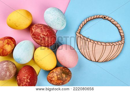 Colored Easter eggs and plywood basket. Chicken painted eggs and cut out plywood basket on colorful paper background. Easter traditional food.