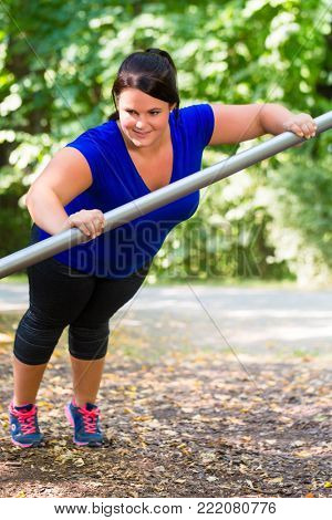 Obese woman doing sport stretching outdoors in park in summer