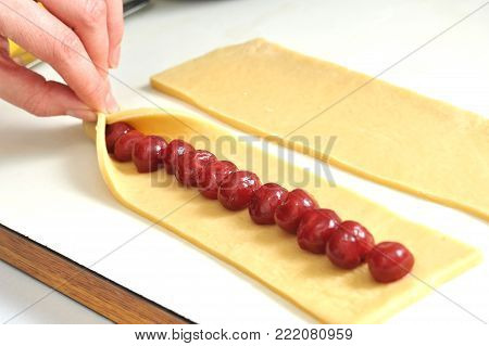 Preparation of cookies in the form of sticks with cherry filling for the cake Monastic cottage. Process of pinching a dough with female hands.