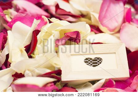 The concept of Love, Wedding, Proposal, Anniversary, St. Valentine's Day, Mother's Day with a wooden casket on red, pink and white rose petals, close up