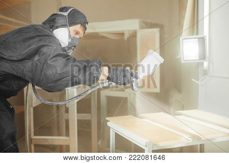 Man in respirator mask painting wooden planks at workshop. Male applicate paints and varnishes. Pneumatic spraying on wooden timber with spray paint gun
