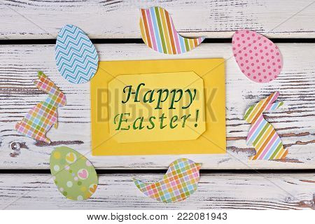 Easter greeting card and papercut figures. Yellow Easter greeting card and composition of animalistic paper cutouts on white wooden background, top view.