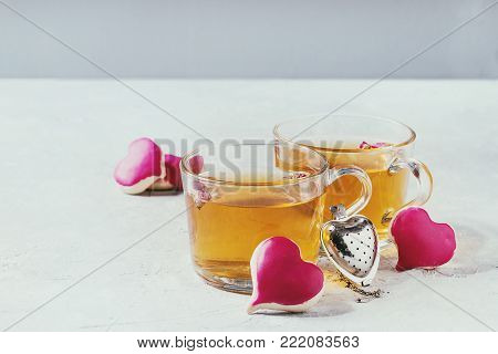 Love Valentines day greeting card with two glasses of hot tea and heart shape homemade cookies with pink icing and tea strainer over white table. Copy space