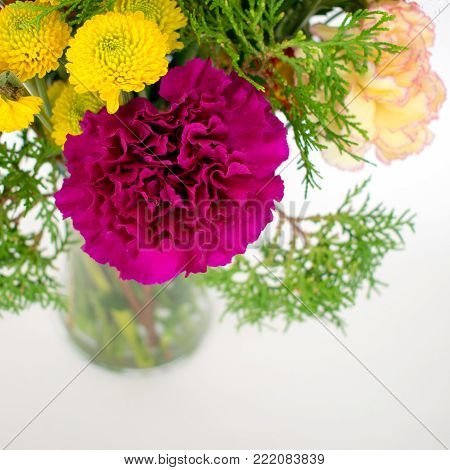 A gorgeous purple carnation is the focal point in this arrangement with several yellow flowers.