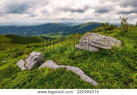 grassy slopes of Carpathian mountains. huge boulder on the edge of a hill side. mountain ridge under the cloudy sky in summer time