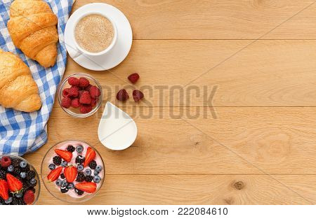 Rich continental breakfast background. French crusty croissants, yogurt, sweet berries and hot coffee for tasty morning meals. Delicious start of the day. Top view, copy space on natural wood