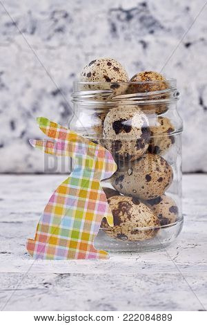 Quail eggs in jar and paper rabbit. Cut out paper patterned rabbit and quail eggs on blurred background. Easter food and traditions.
