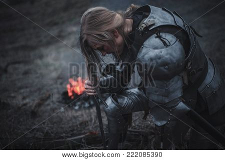 Girl in image of Jeanne d'Arc kneels in armor and with sword in her hands against background of fire, smoke and dry grass. Closeup.