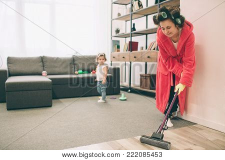 mother and baby together engaged in housework. She is washing the floor of the mop. Housewife and kid doing homework. Woman with little child in the living room. Homemaker doing many tasks while looks after her infant.