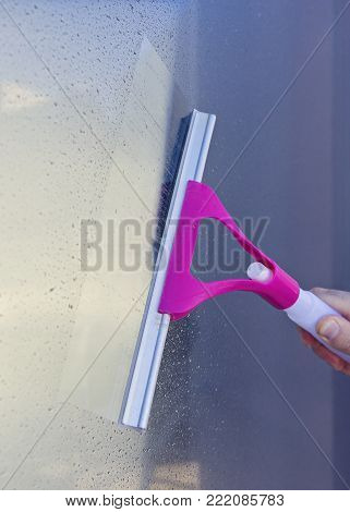 Male hand cleans glass window with Window Wiper Squeegee Seasonal Spring cleaning concept verical